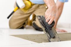 home improvement, renovation - handyman laying tile - stock photo