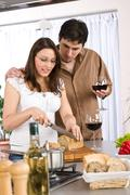 Cooking - happy couple together in modern kitchen Stock Photos