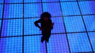 Woman dances at dark discotheque with illuminated floor Stock Footage