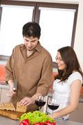 Happy couple cut bread in modern kitchen Stock Photos
