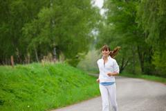 Stock Photo of jogging - sportive woman running on road in nature