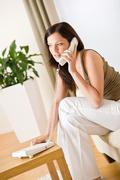on the phone home - young woman calling in lounge - stock photo