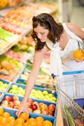 grocery store - smiling woman shopping choose fruit - stock photo