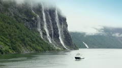 Ship floats by fiord near Seven Sisters waterfall on mountain - stock footage