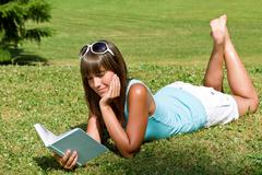 Stock Photo of smiling young woman lying down on grass with book