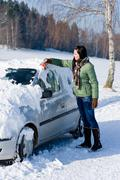 Winter car - woman remove snow from windshield Stock Photos