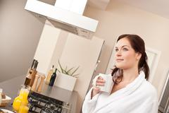 Stock Photo of young woman enjoying cup of coffee in kitchen