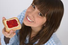 Happy teenager in pajamas eating healthy toast Stock Photos