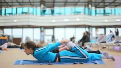 woman in sports hall does gymnastics with others lying on rug - stock footage