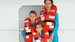 Mother with son and daughter in life jackets stands on ship deck Stock Footage