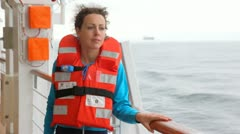 Woman in red life jacket looks at waves from ship board Stock Footage