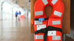 Red life jacket on ship deck close up against walking people Stock Footage