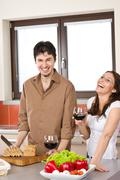 happy couple in modern kitchen drink red wine - stock photo