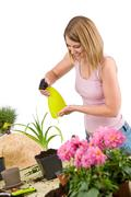 Stock Photo of gardening - woman sprinkling water to plant