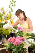 Gardening - woman with watering can and flowers Stock Photos