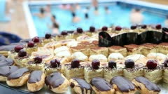 Full dish of sweet cakes and eclairs in front of pool Stock Footage