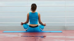 Woman in blue sits back in lotus pose on ship deck Stock Footage