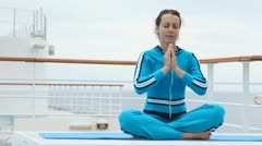 On ship deck woman on rug sits in lotus pose Stock Footage