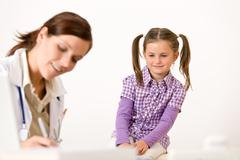 Stock Photo of female doctor write prescription for child