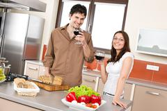 Happy couple in modern kitchen drink red wine Stock Photos