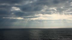 Sea, clouds and beam of sun which are making way from under them Stock Footage