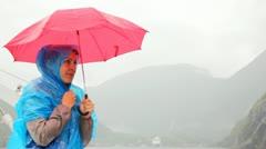 Woman under umbrella freezes against rocky landscapes Stock Footage