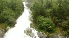 Mighty falls on flowing down from wood rocks during rain Stock Footage