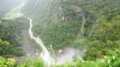 mountains with falls, fiord and small houses in valley below - stock footage