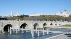 Bridge Puente de Segovia stands against Almudena Cathedral - stock footage
