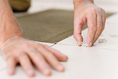Home improvement - handyman placing tile spacer Stock Photos
