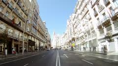 Bus go on Gran Via Street along walking tourists Stock Footage
