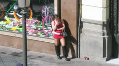 Young girl in red dress stands near shop show-window on street Stock Footage