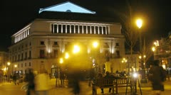 Tourists walk in front of Teatro Real in evening Stock Footage
