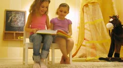 Two girls read book near toy horse in playroom Stock Footage