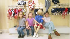 Two girls and boy sit near manikin in shopping center - stock footage