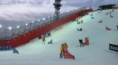 Athletes go down on stage of World Cup on snowboard at evening Stock Footage
