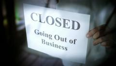 Placing a Going Out of Business Sign on Glass Door - stock footage