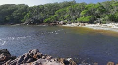 Two young adults swimming in the morning at Bittangabee Bay Beach, Australia Stock Footage