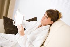 Young woman read book on sofa wearing bathrobe Stock Photos