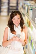 Shopping cosmetics - smiling woman with moisturizer Stock Photos