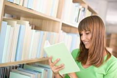 Stock Photo of student in library - happy woman read book