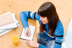 Stock Photo of teenager girl home - student write homework