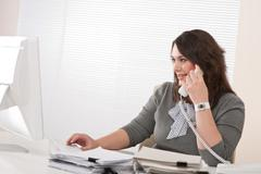 Attractive executive woman on phone at office Stock Photos