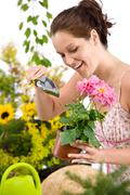 Stock Photo of gardening - woman holding flower pot and shovel