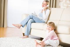 mother and child in living room watch television - stock photo