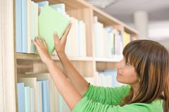 Student in library - happy woman choose book Stock Photos