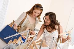 fashion shopping - two happy woman choose sale clothes - stock photo