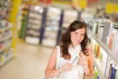 shopping cosmetics - woman with moisturizer - stock photo