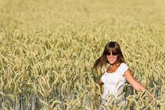 happy woman in corn field enjoy sunset - stock photo