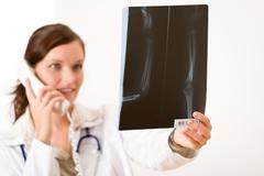 female doctor with x-ray and phone - stock photo